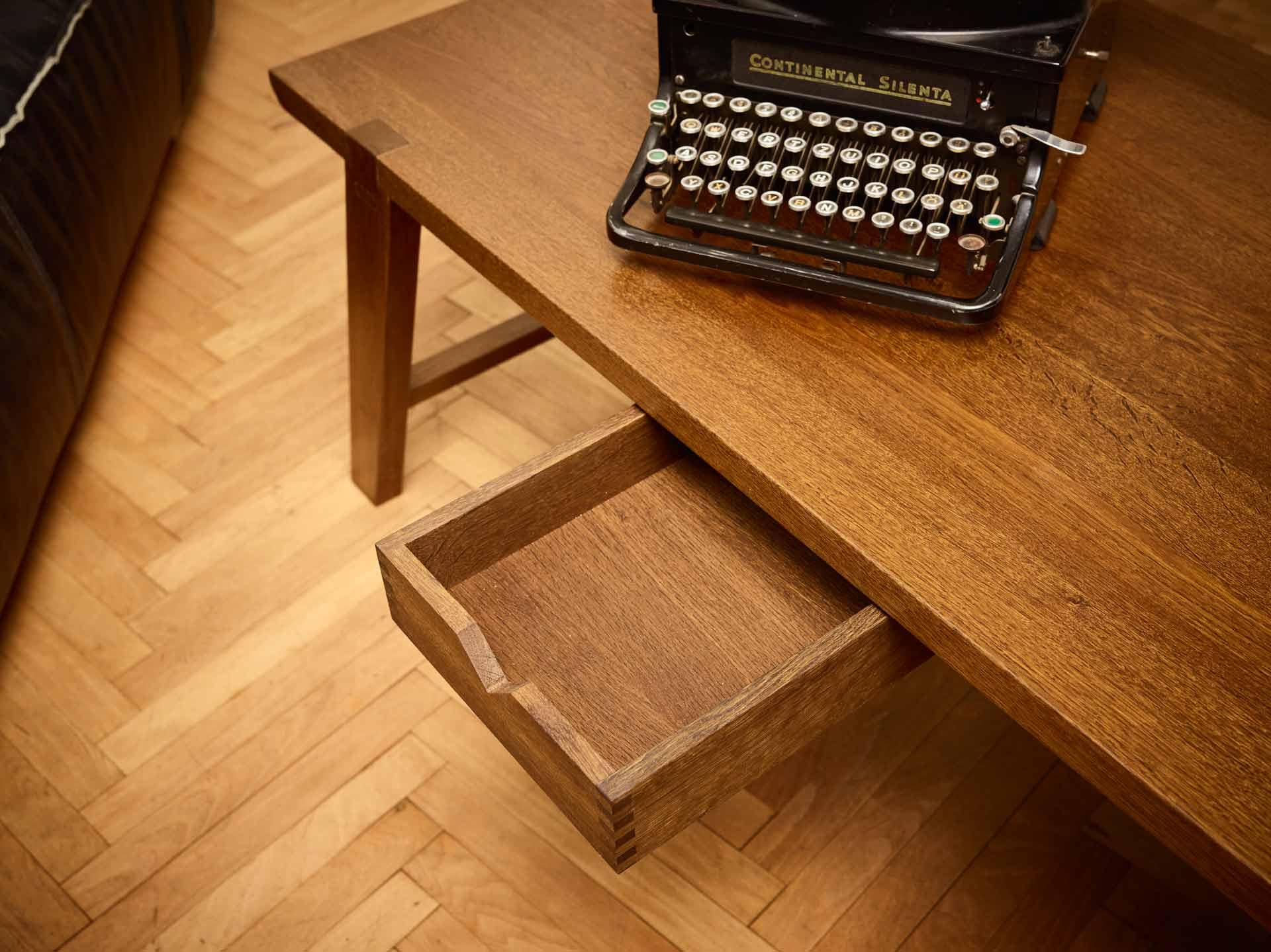Couchtisch mit alter Schreibmaschine und geöffneter Lade