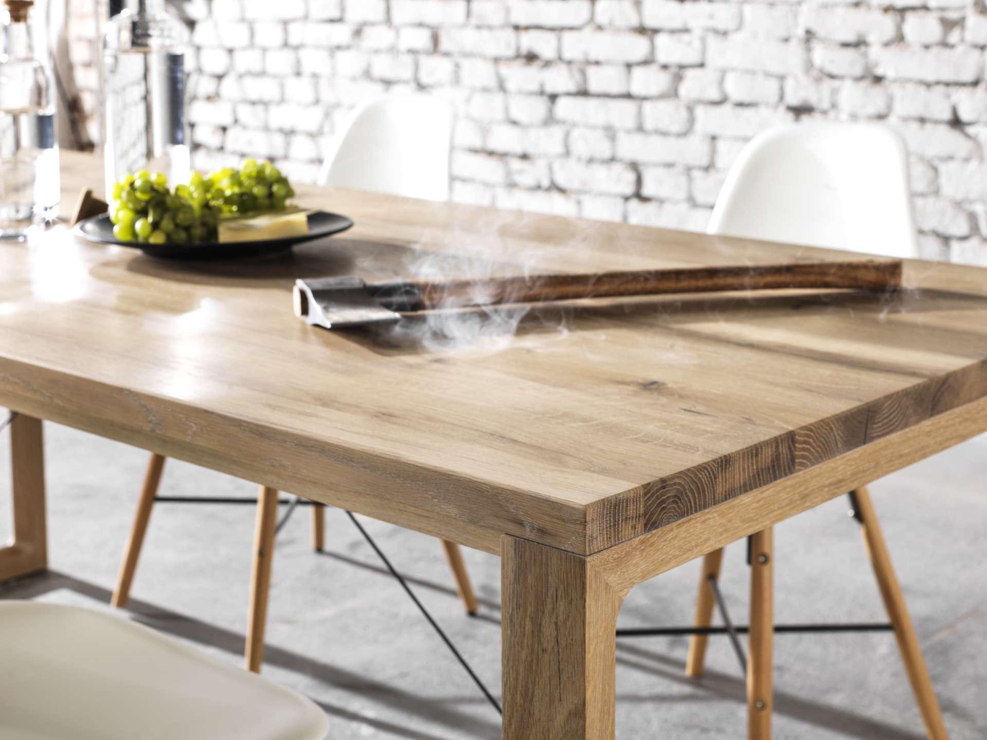 Eichentischplatte aus Massivholz weiß geölt. Auf dem Tisch liegt eine Axt mit Rauch umgeben.