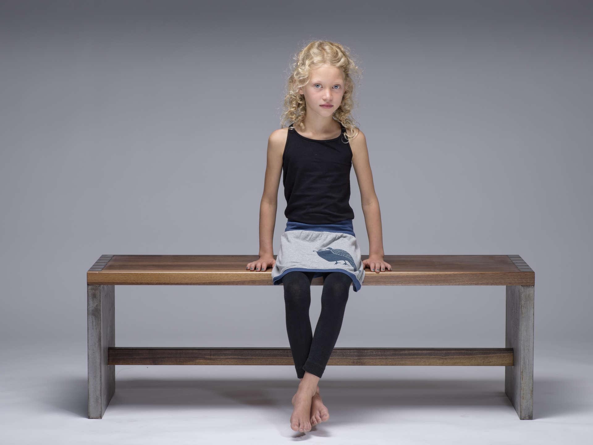 Model sitzend auf Massivholz Beton Sitzbank.