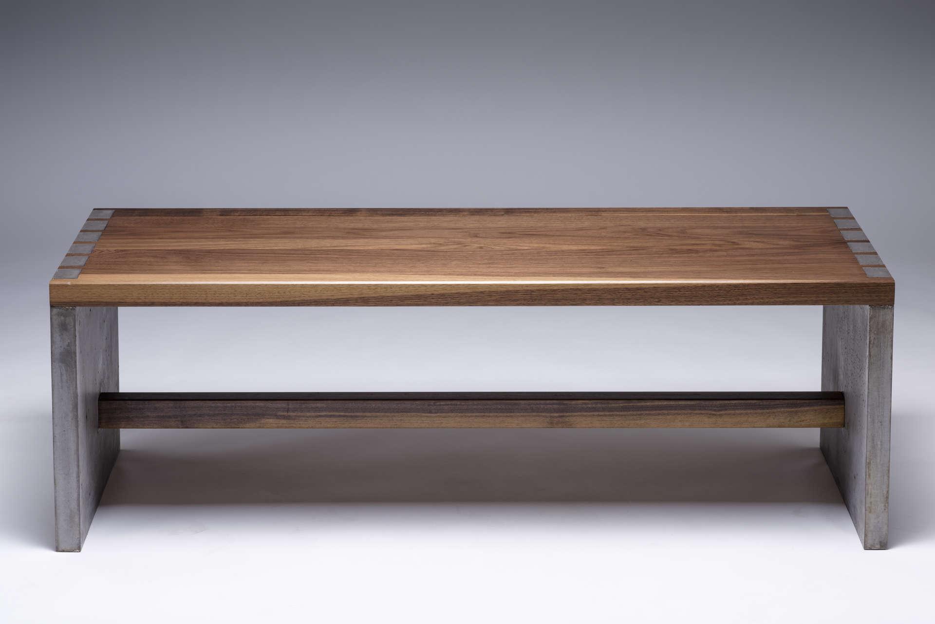 Vorderansicht der Sitzbank. Sitzfläche aus geöltem Nussholz. Seitenteile aus Beton.
