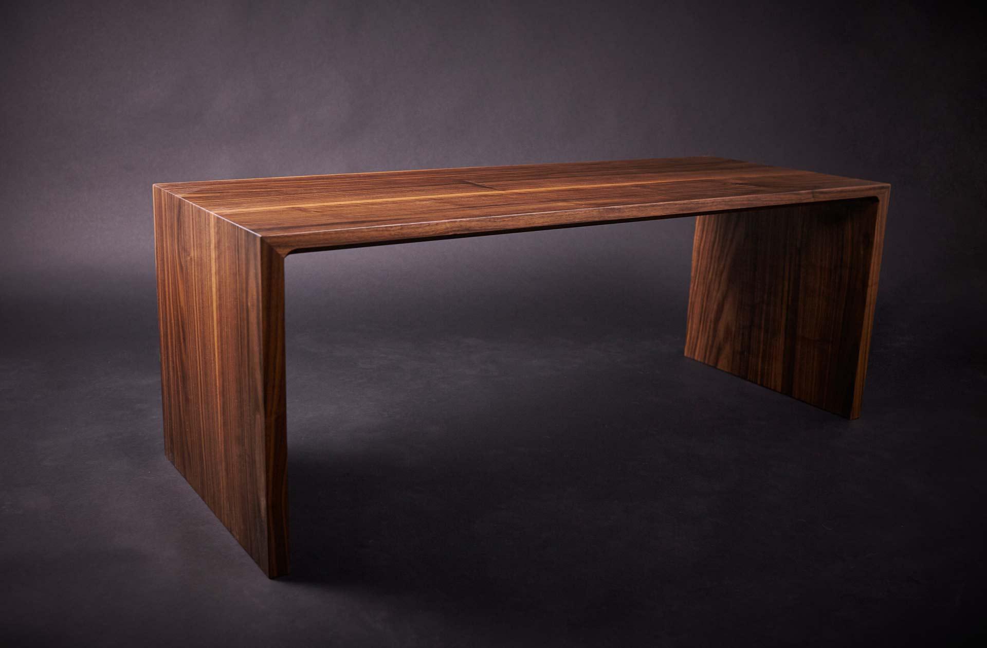 Designer Sitzbank aus massiven Nussholz auf schwarzem Hintergrund in der Seitenansicht.