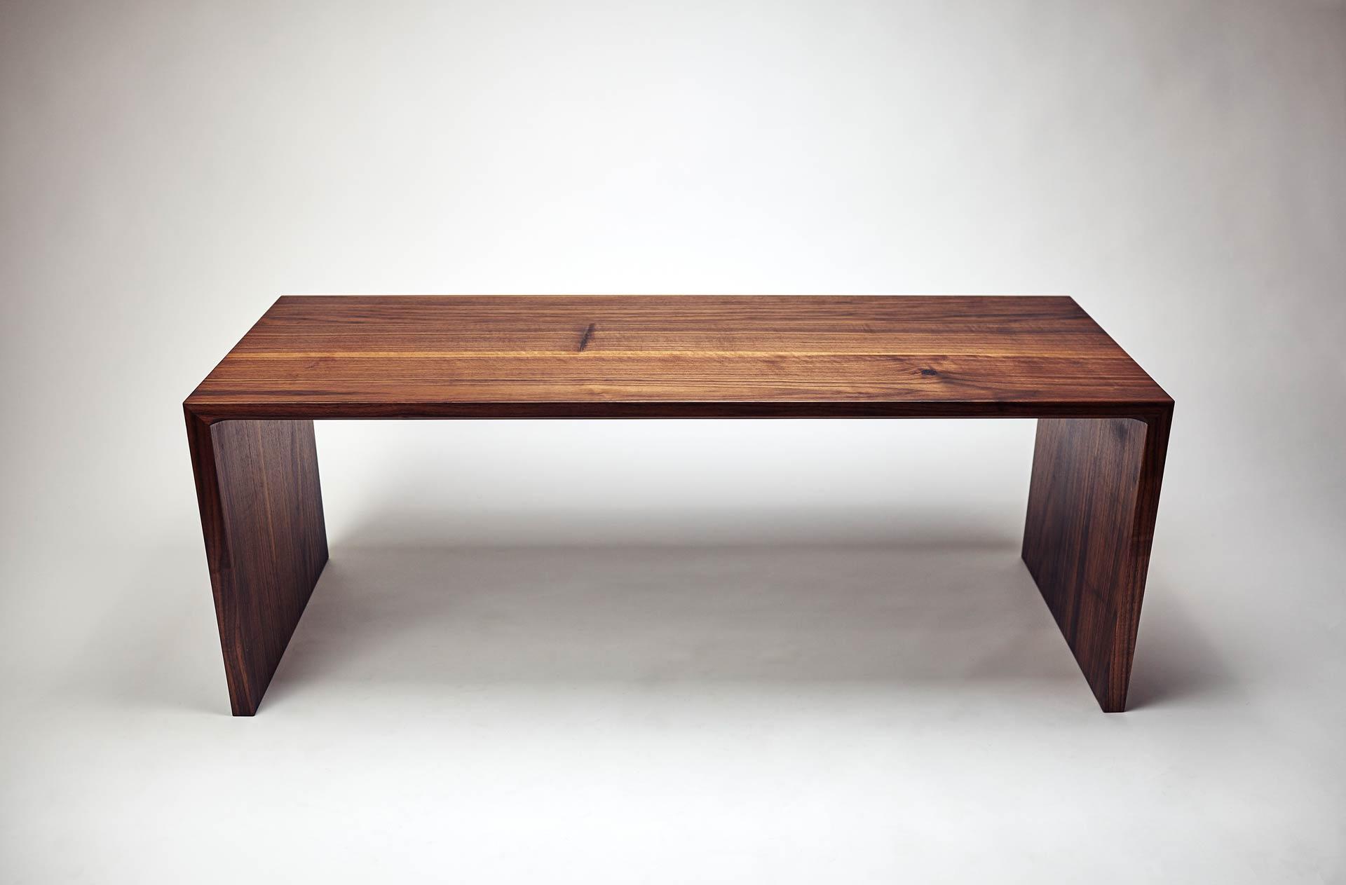 Designer Sitzbank aus massiven Nussholz. Die Sitzfläche wirkt durch die schräge Fräsung auf der Längsseite dezenter als die Seitenteile.