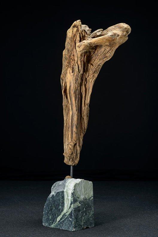 Schwemmholzskulptur stehend auf Steinsockel.