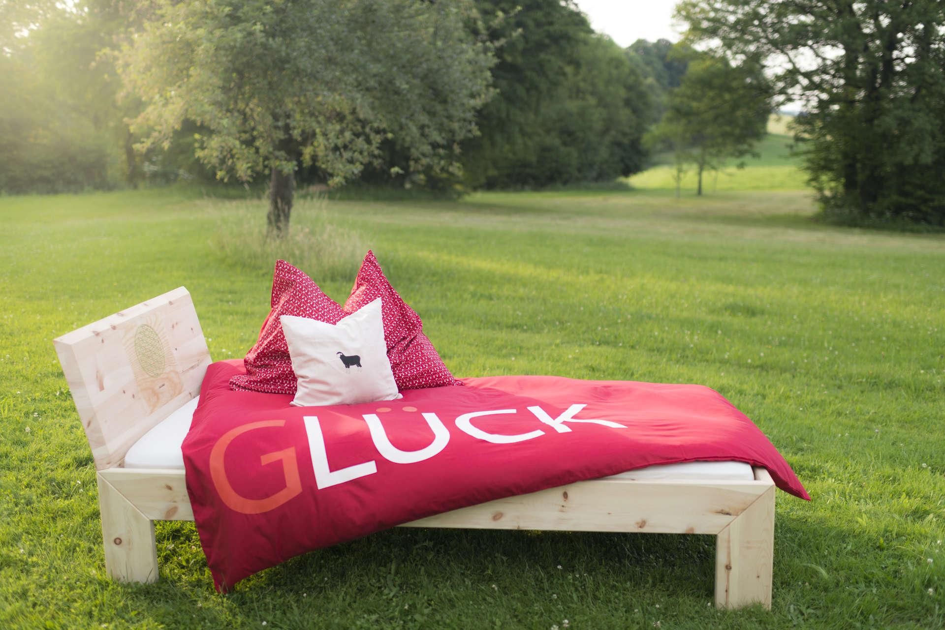 Zirbenbett in der Natur. Bettwäsche mit der Aufschrift Glück.